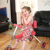 Summer sitting on her custom made folding trike with back support