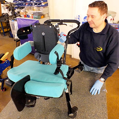A DEMAND engineer disassembles a paediatric chair for refurbishing