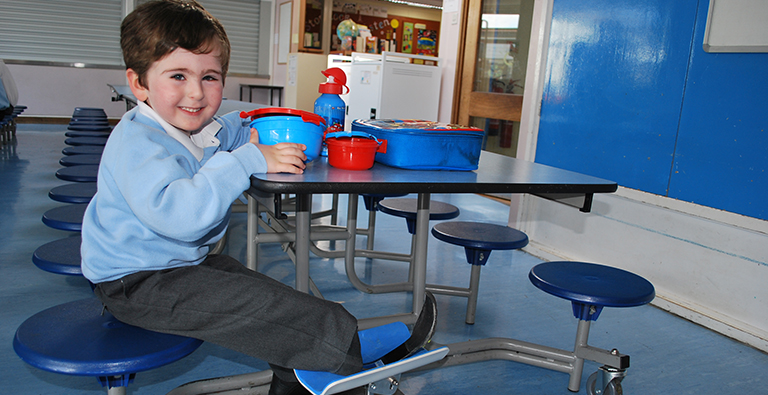 A young boy with an artificial leg uses his custom made leg stand at school