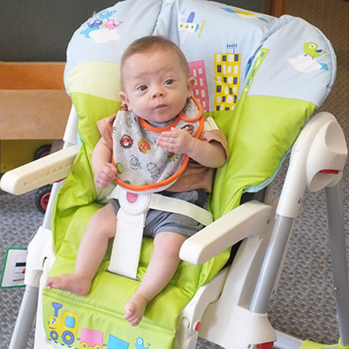 Jenson sitting in his modified high chair