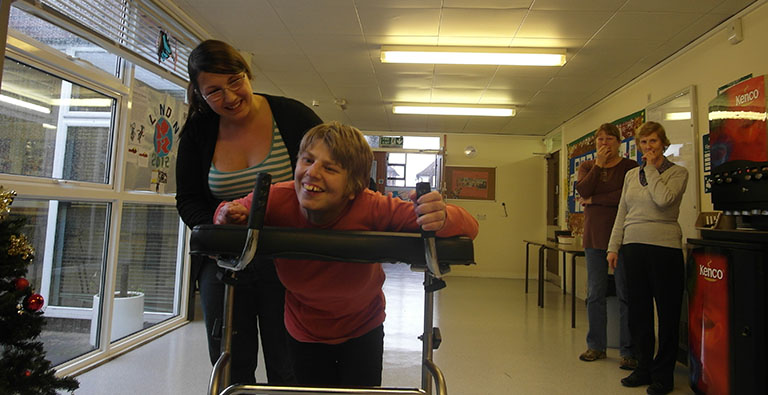 Claire walks with the adapted walking frame