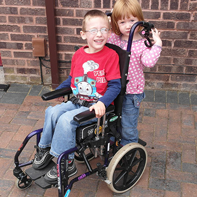 Nathaniel in his wheelchair with his sisten standing on the buggy board