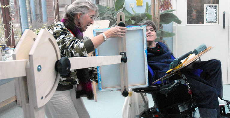 An artist and her assistant set up the easel to begin painting