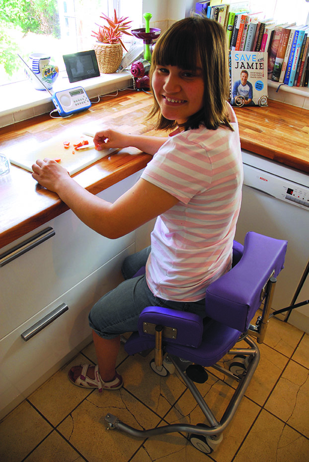 Natasha using the perching stool in her kitchen