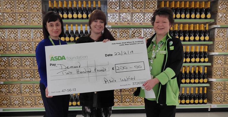 ASDA staff present a cheque to Denise Gillies of DEMAND