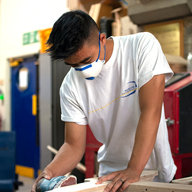 DEMAND Designer sanding wood in workshop